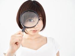 虫眼鏡で観察する女性