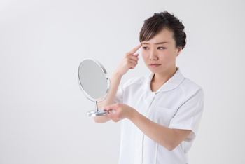 鏡で眉毛を確認する女性
